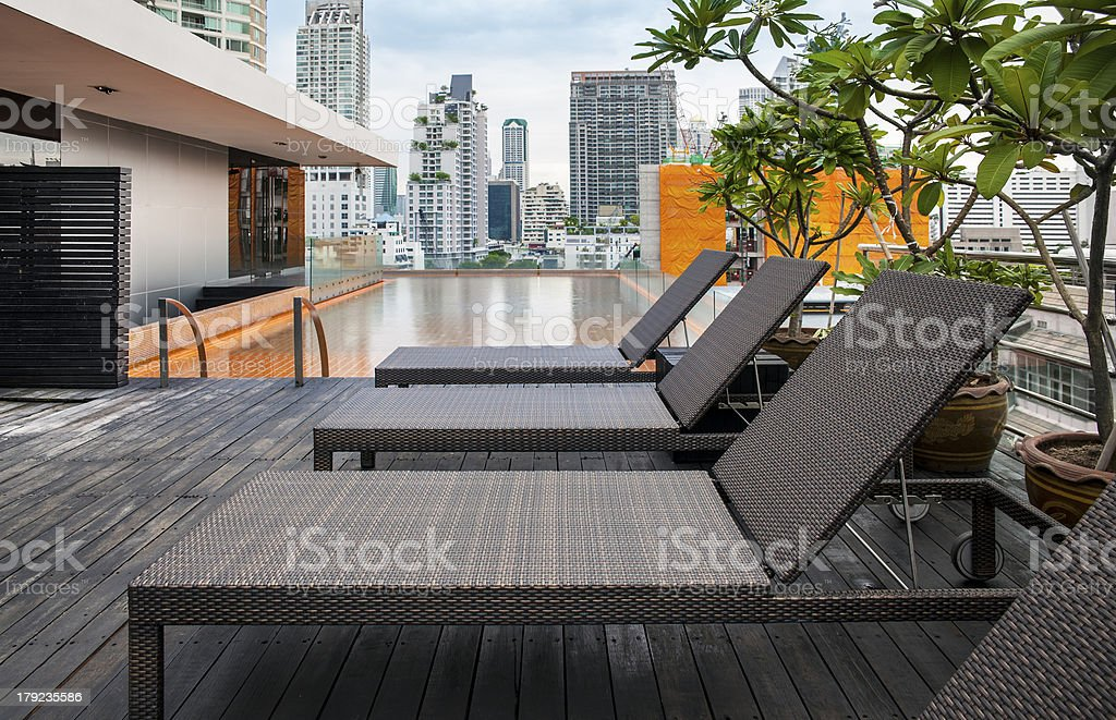 Sunbeds next to a swimming pool on rooftop. stock photo
