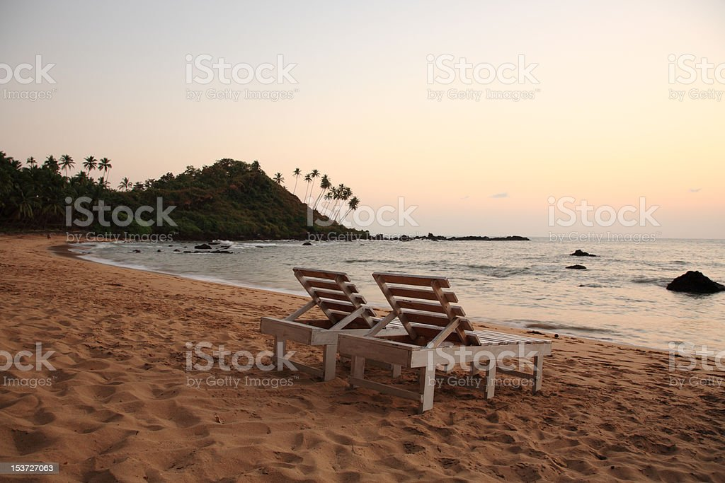 Sunbeds on the beach at sunset stock photo