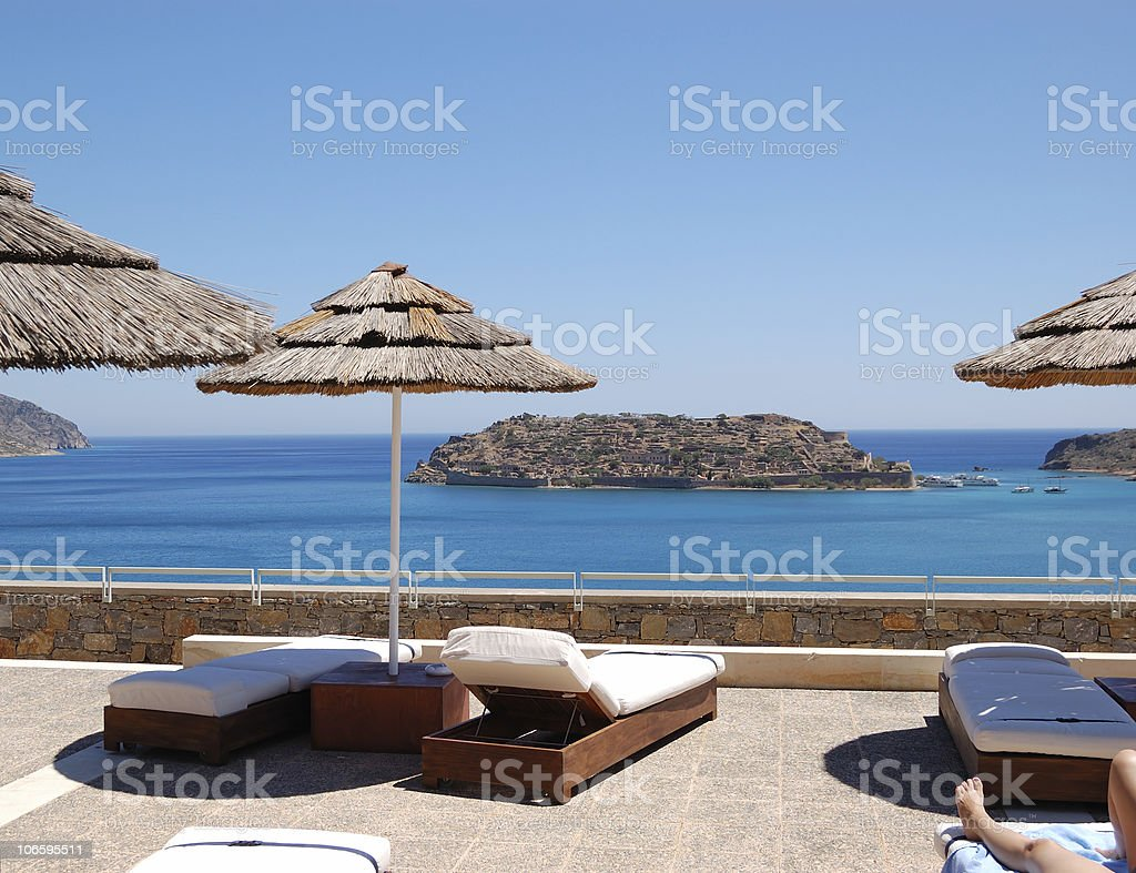 Sunbeds with a view on Spinalonga Island, Crete, Greece royalty-free stock photo