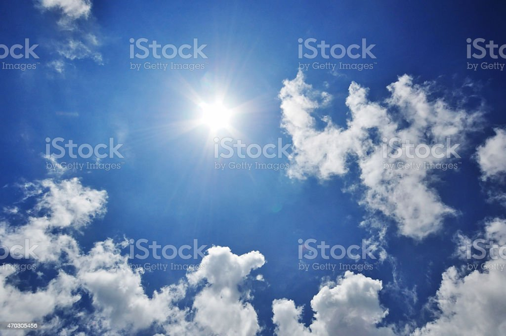 Sunburst and blue sky background with fluffy clouds. stock photo