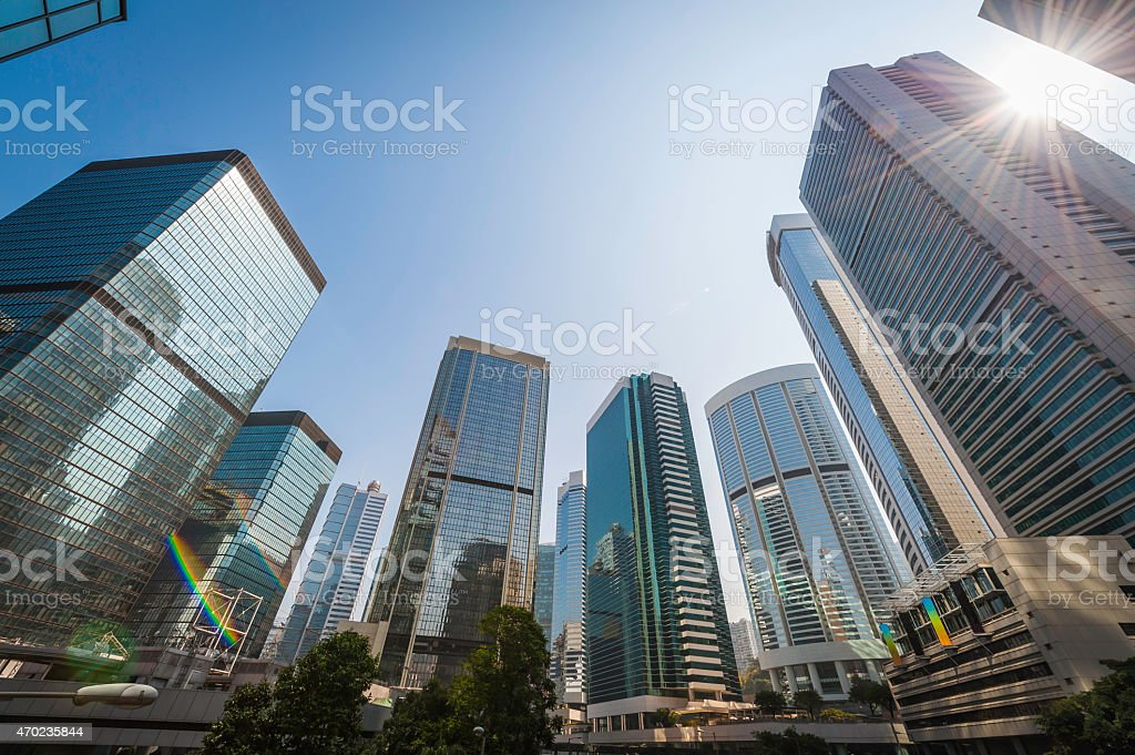 Sunburst skyscrapers soaring into blue skies crowded cityscape Hong Kong stock photo