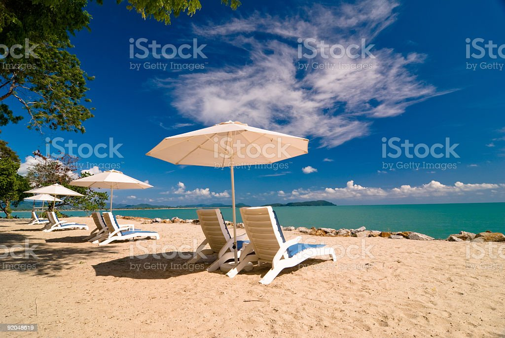 Sunchairs and umbrella on Beach stock photo