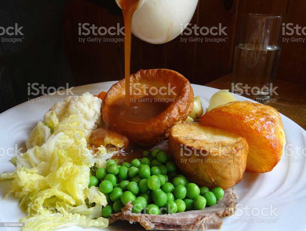 Sunday roast dinner, beef, Yorkshire pudding, pouring gravy jug, roast potatoes stock photo