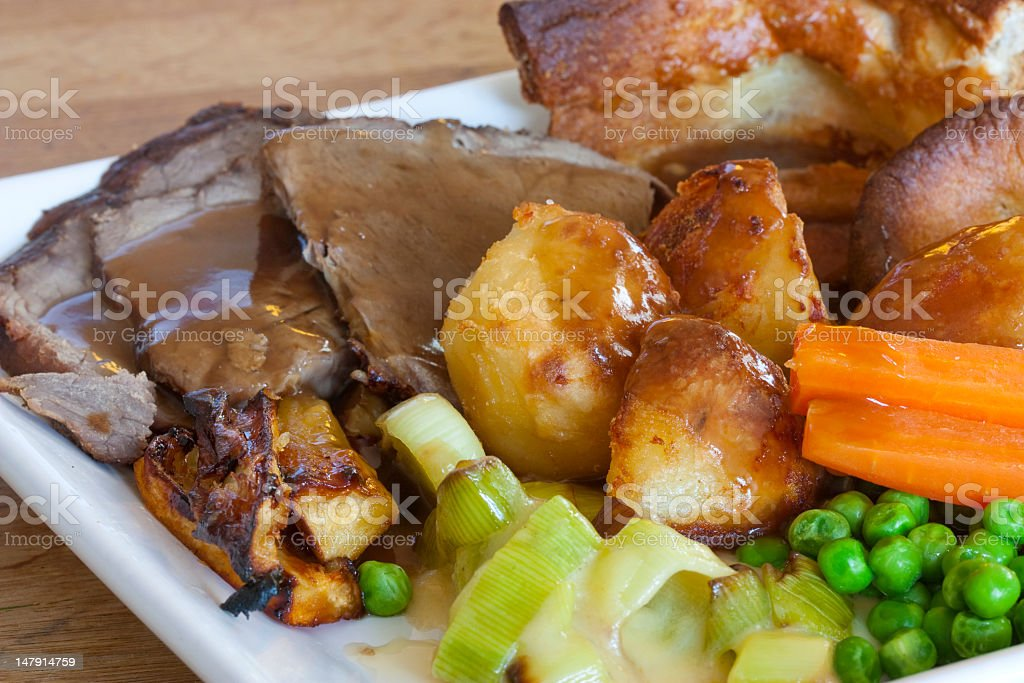 A Sunday roast with pork, potatoes, carrots and peas stock photo