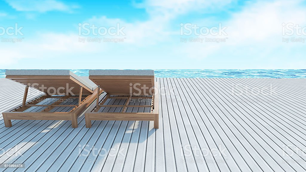 Sundesk chairs on white wooden floor with sea view background stock photo