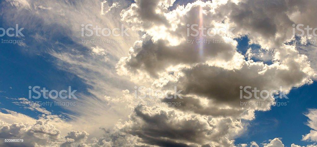 Sundog flare in high clouds in a bright blue sky stock photo