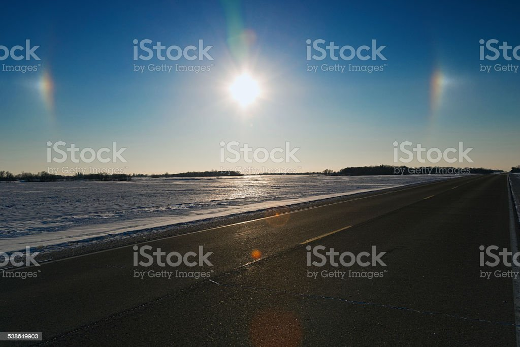 Sundogs over a Rural Paved Two Lane Highway stock photo