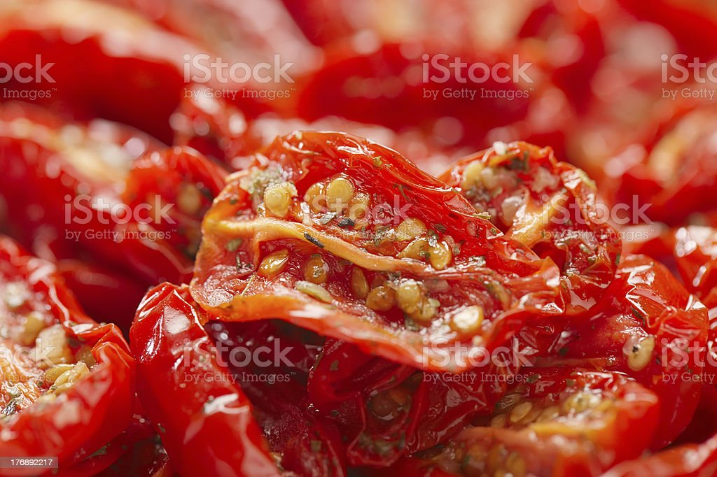 sun-dried tomatoes with olive oil, background, shallow dof stock photo