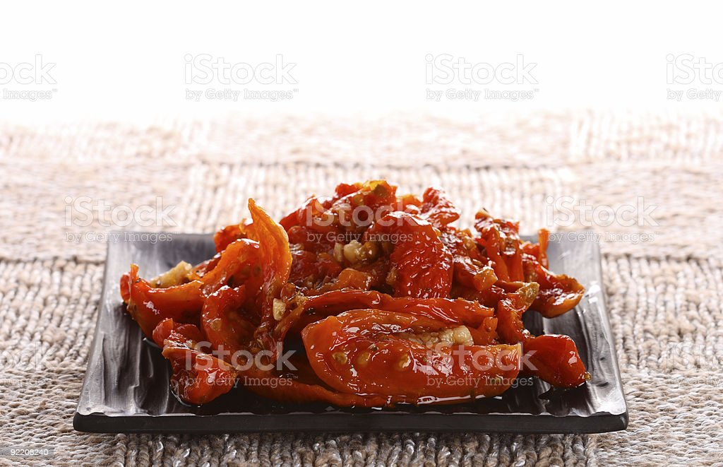 sun-dried tomatoes with olive oil on  plate knitted fabric background stock photo