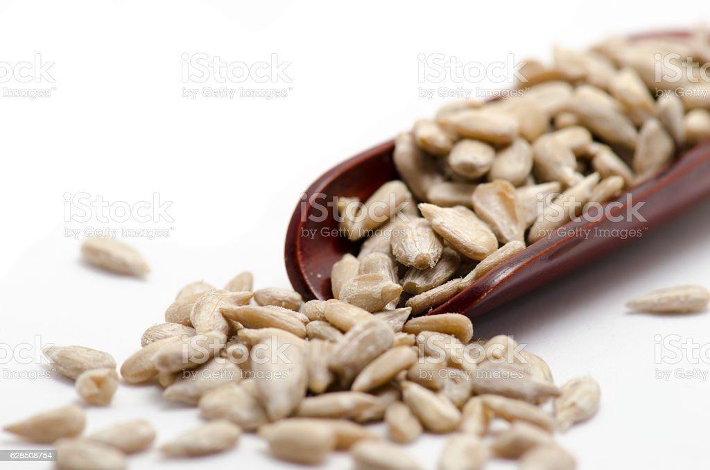 Sunflower seeds pilled in wooden spoon isolated on white backgroud stock photo