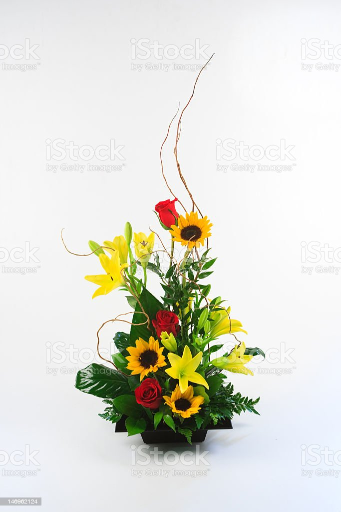 Sunflowers and roses in a tall flower arrangement stock photo