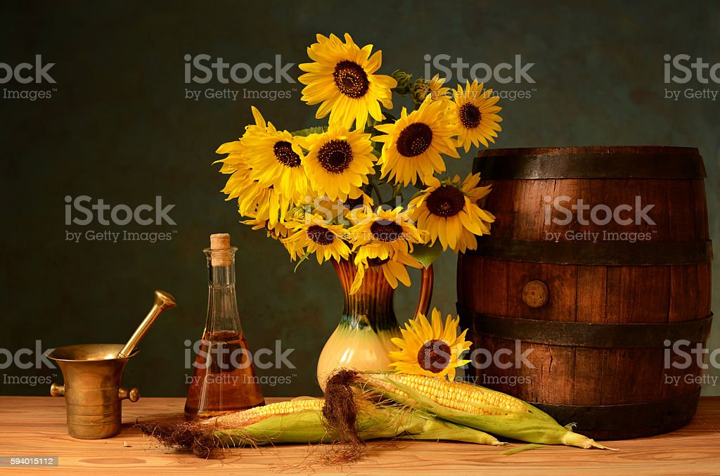 Sunflowers in a vase, wooden barrel, brandy in the bottle stock photo