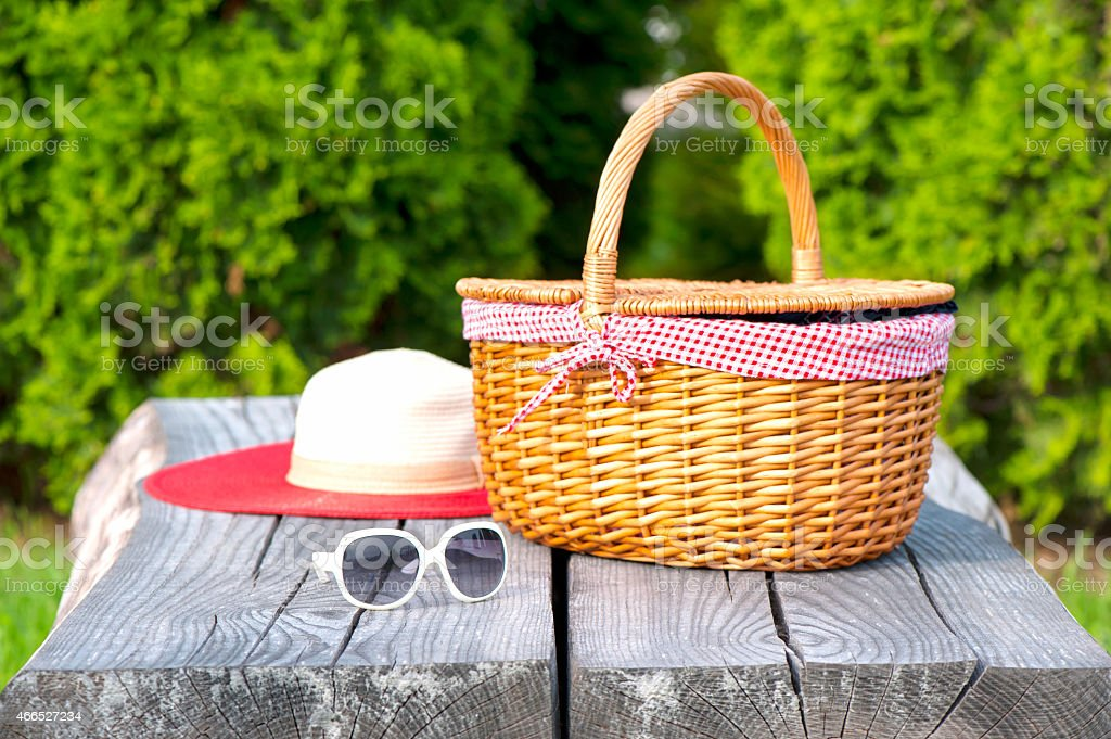 Sunglasses and hat with a picnic basket on a picnic table stock photo