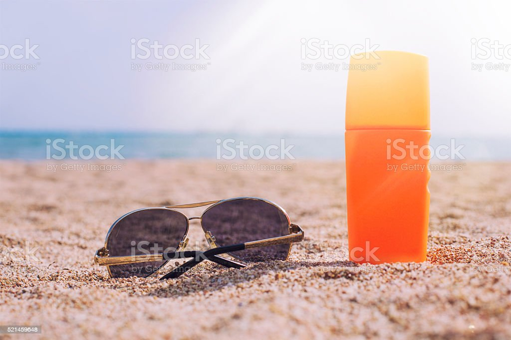 Sunglasses and sun cream in the sand against the sea stock photo