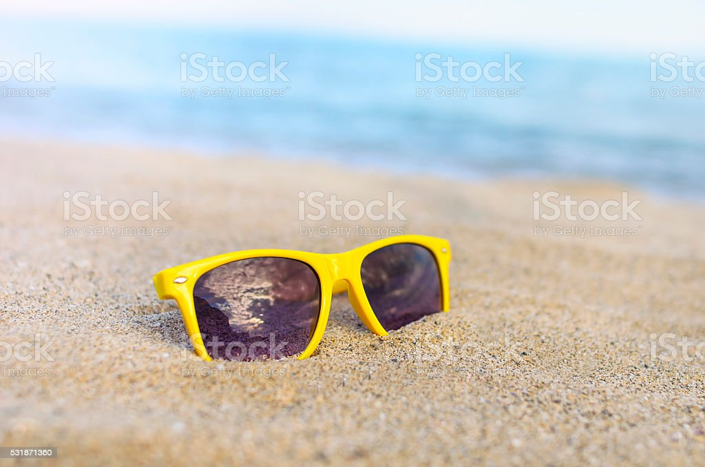Sunglasses beach against backdrop of the sea stock photo