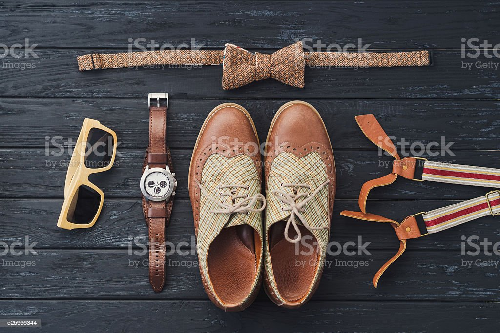 Sunglasses, bow tie, shoes, watch, suspenders on black wooden background stock photo
