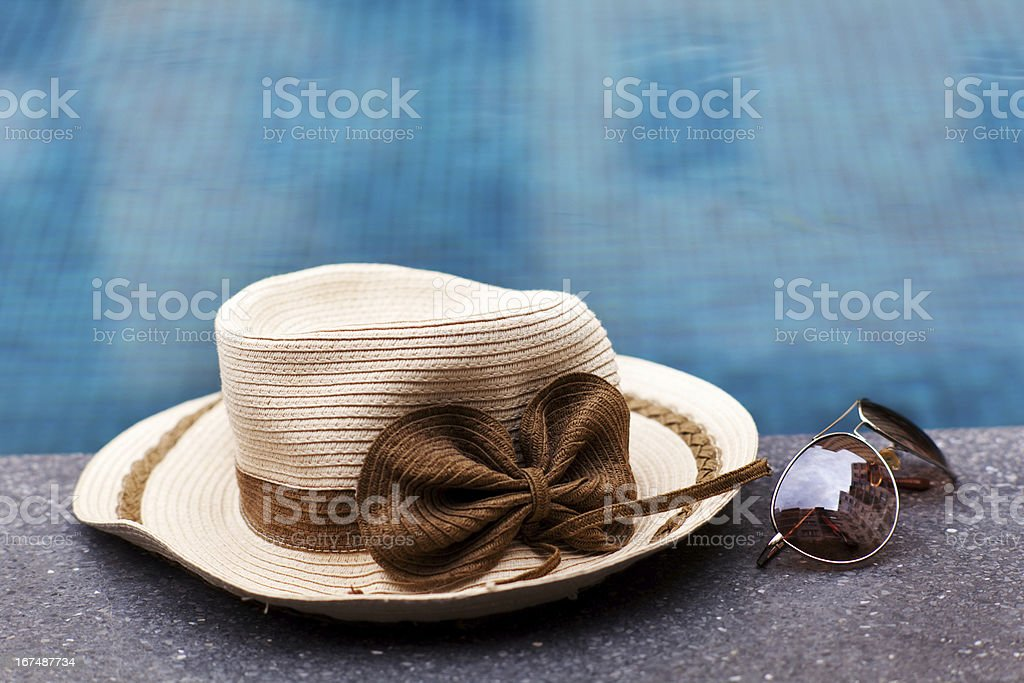 Sunglasses by a blue pool in city town royalty-free stock photo