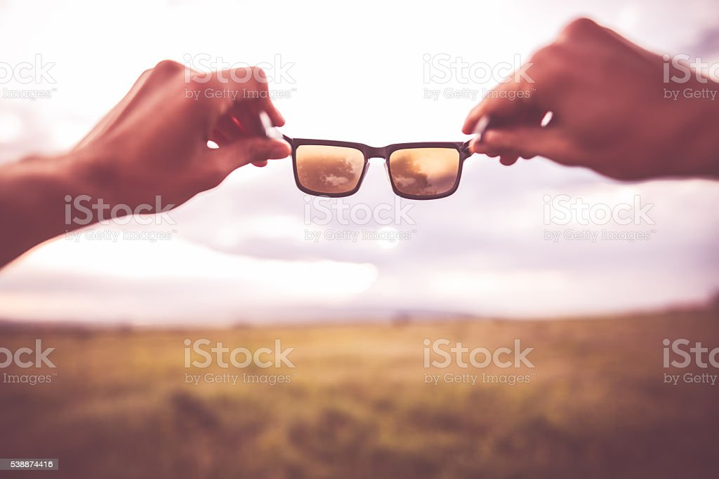 Sunglasses in hands outdoors stock photo