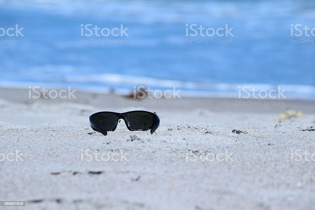 Sunglasses Left Behind on Beach Sand with Blue Ocean Background stock photo