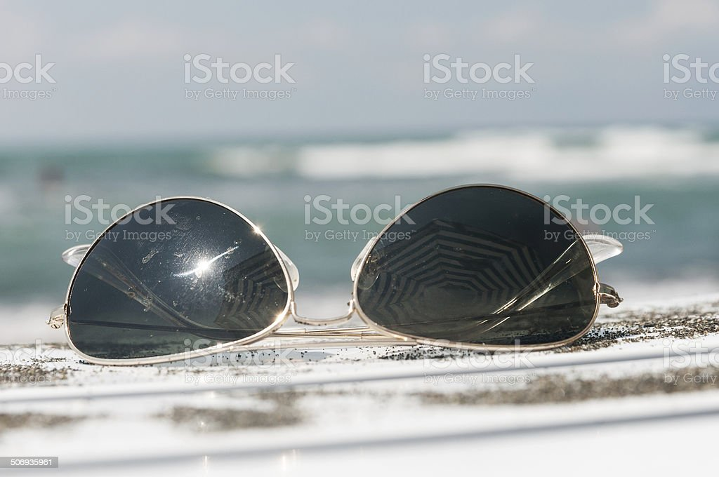 sunglasses on a lounger and sand stock photo