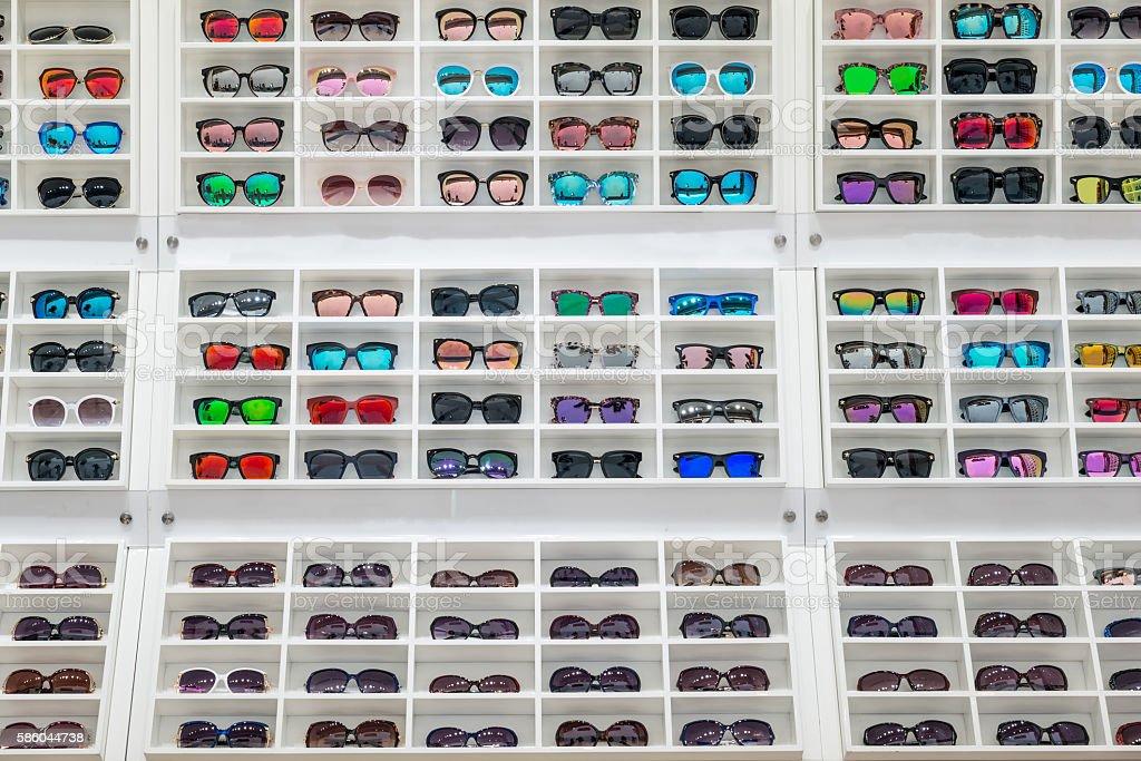 Sunglasses on sale display shelf in sunglasses shop. stock photo