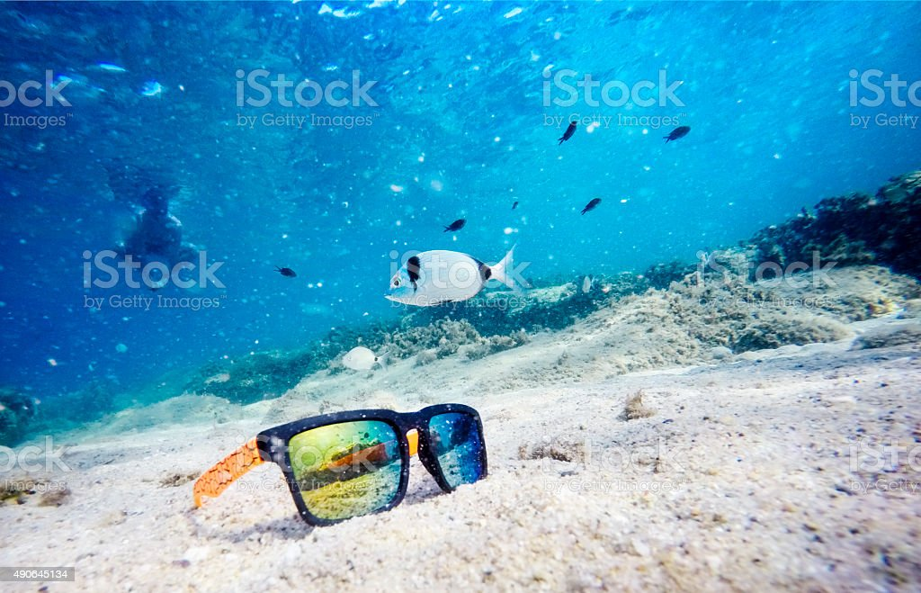 Sunglasses on seabed with fish and diver stock photo