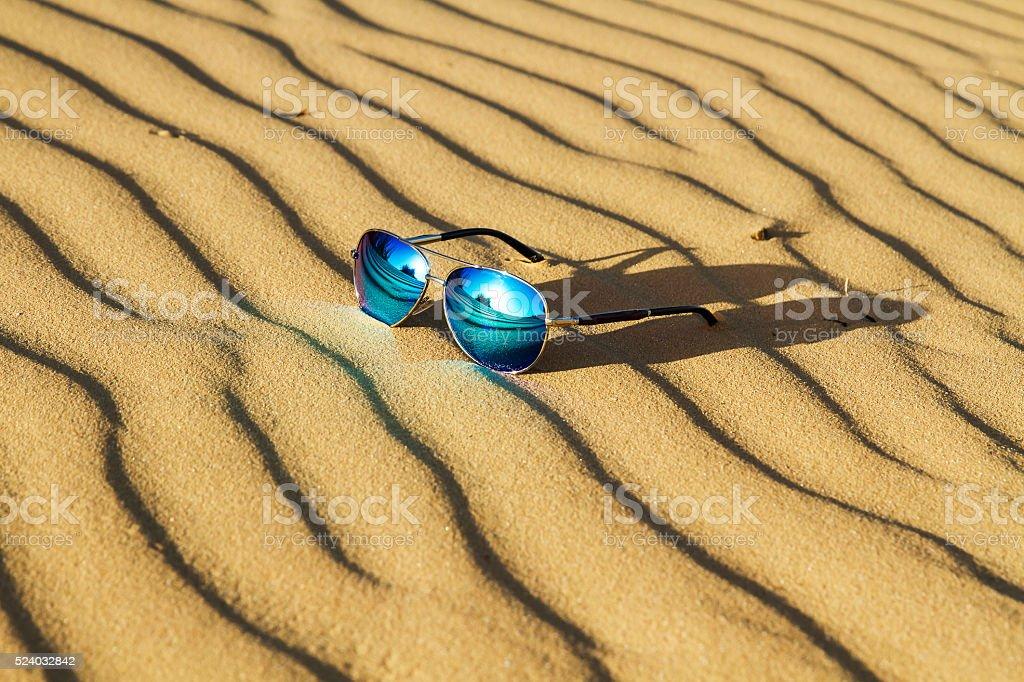 Sunglasses on the sand in the desert. stock photo
