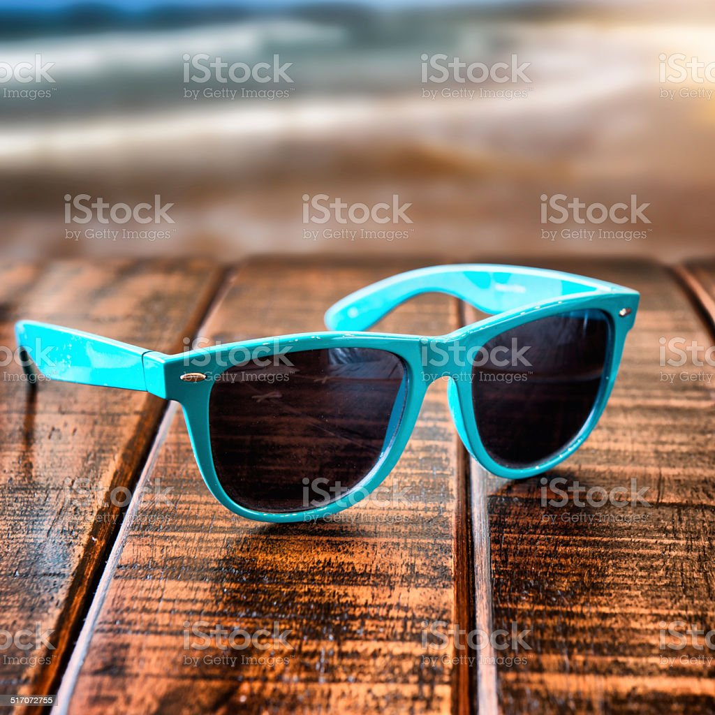 Sunglasses on wooden desk at the summer beach stock photo