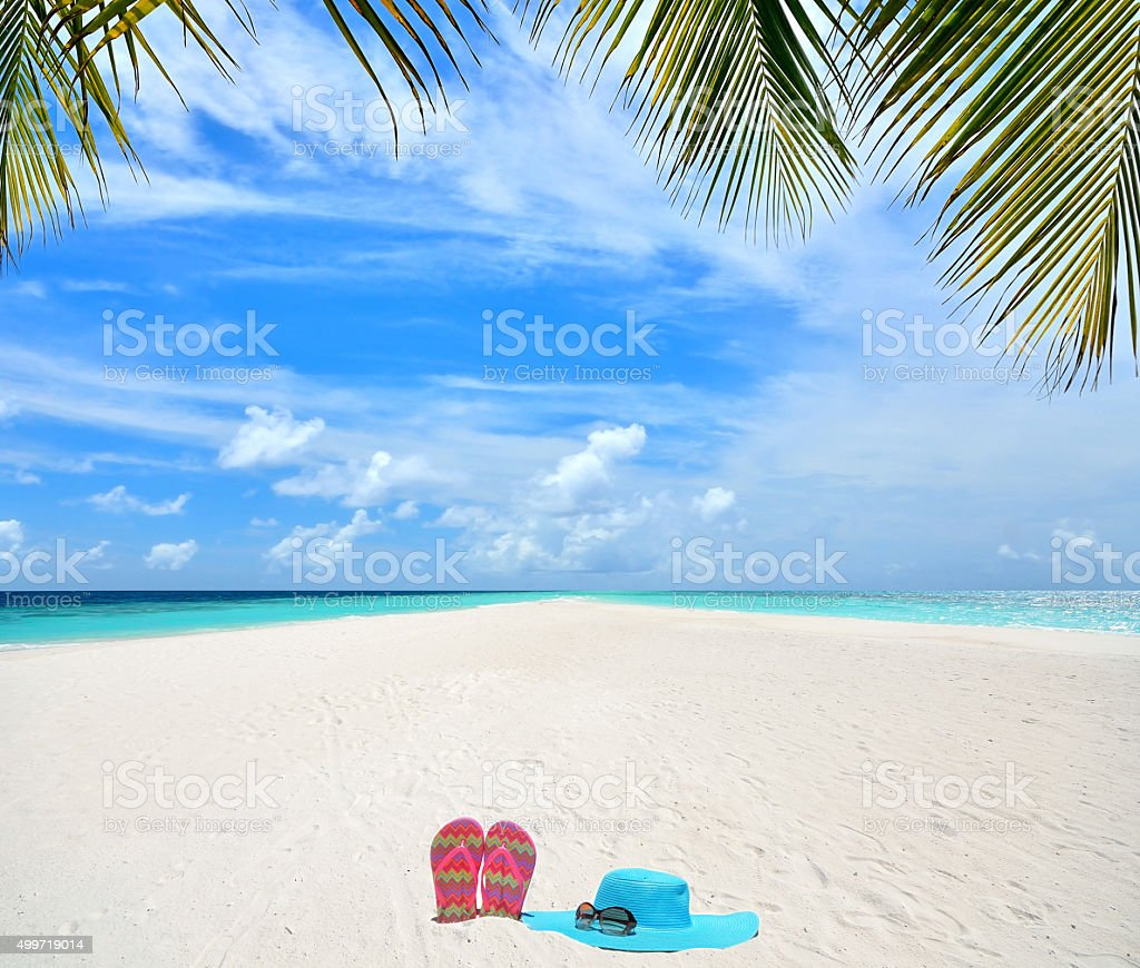 Sunhat with sunglasses and flip-flop at tropical beach stock photo