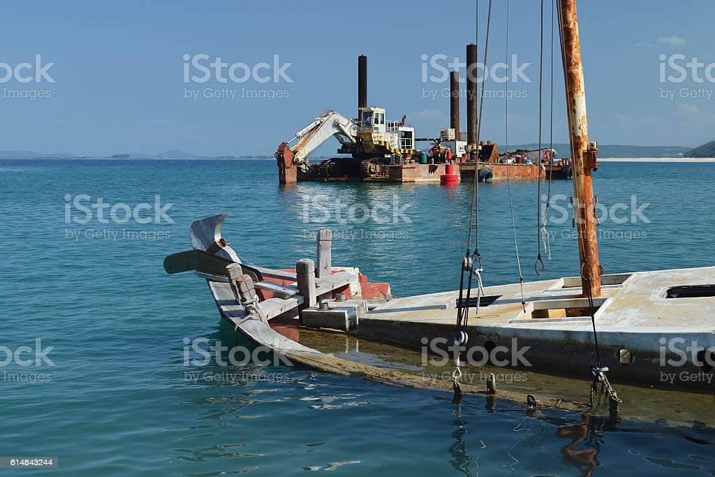 Sunken wooden boat and old rusty dredger stock photo