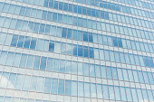Sunlight and clouds reflecting in windows of office building