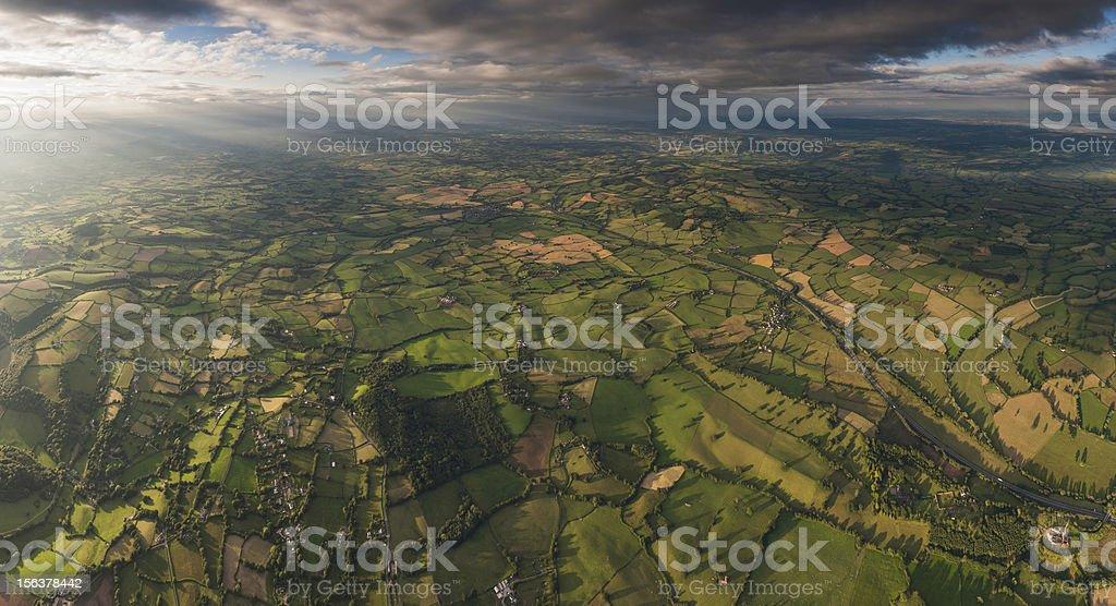 Sunlight on idyllic patchwork landscape aerial panorama royalty-free stock photo