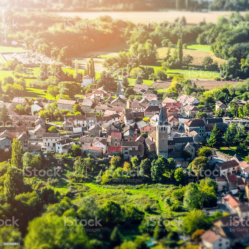 Sunlight on small french village in countryside landscape stock photo