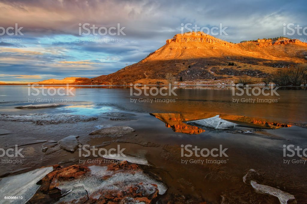Sunlight on the Red Butte with  lake in the foreground stock photo