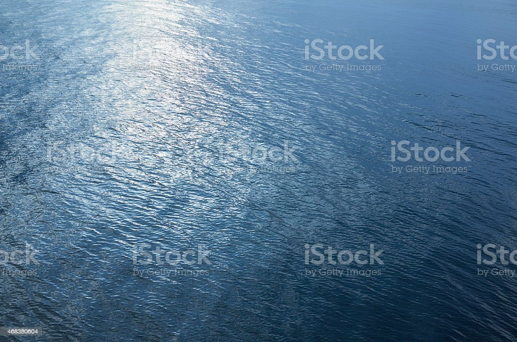 Sunlight reflecting across the surface of a blue ocean stock photo