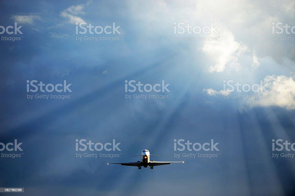 Sunlit airplane flying into sunshine royalty-free stock photo
