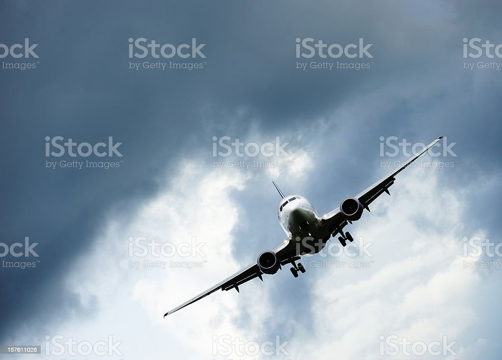 Sunlit airplane taking off against dramatic sky royalty-free stock photo