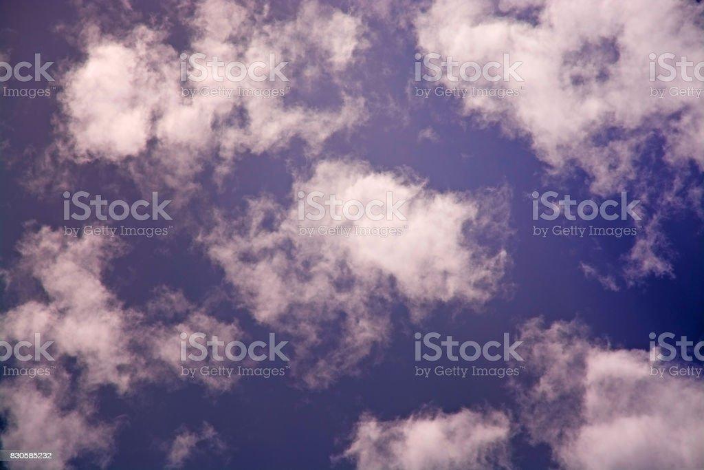 Sunlit clouds on evening sky stock photo