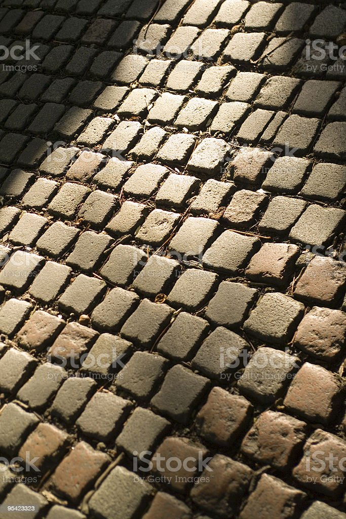 Sunlit cobbled street from above stock photo