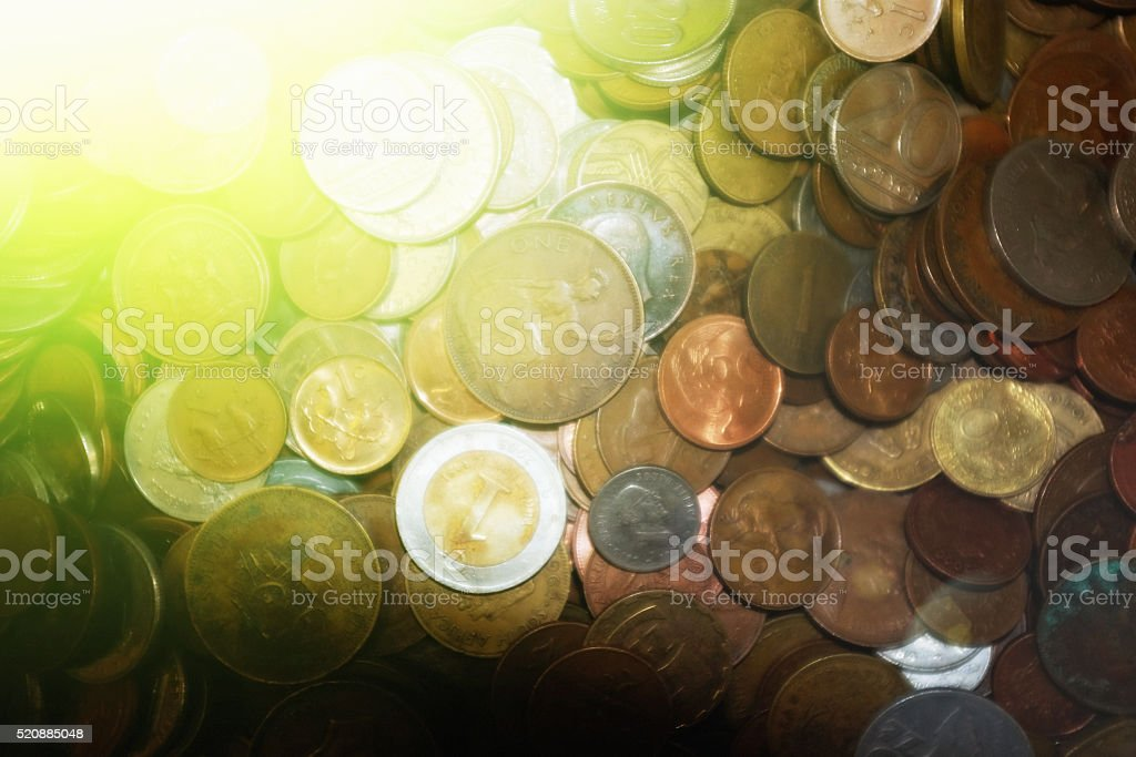 Sunlit coins of many nations and ages for monetary background stock photo
