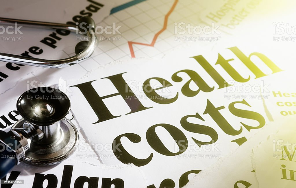 Sunlit headlines on health costs with stethoscope stock photo