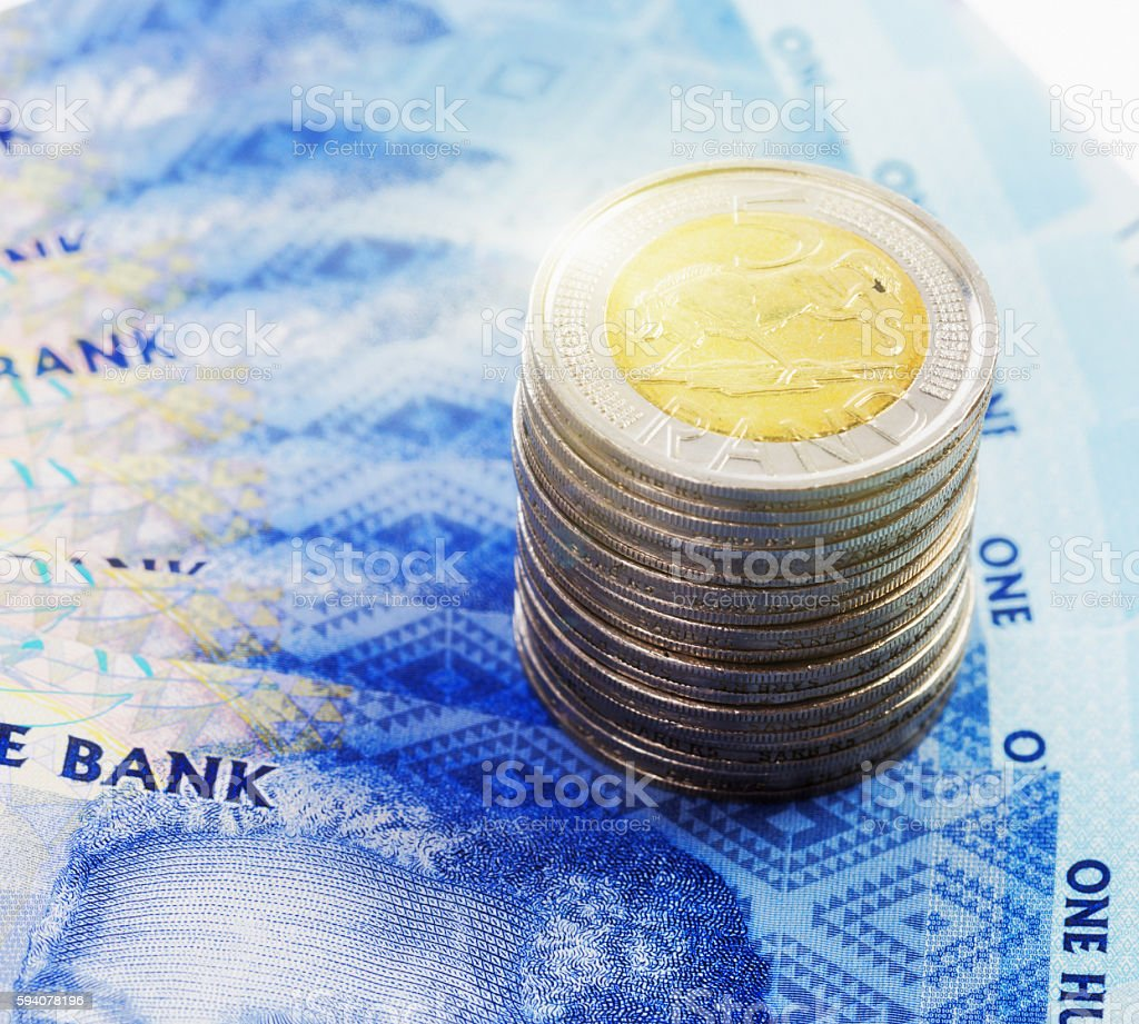 Sunlit stack of South African Five Rand Coins with banknotes stock photo