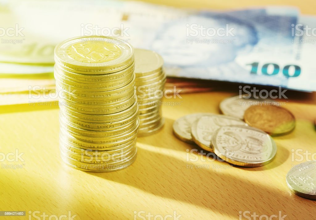 Sunlit stacks of South African currency: banknotes and coins stock photo