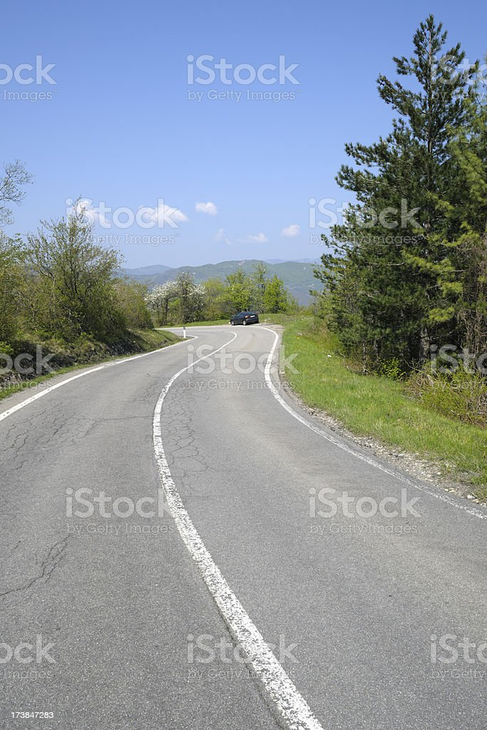 Sunny Country Road with car on bend stock photo