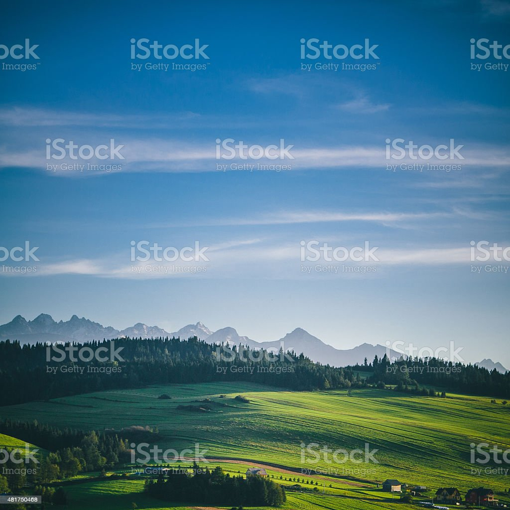 Sunny fields and mountains countryside landscape stock photo
