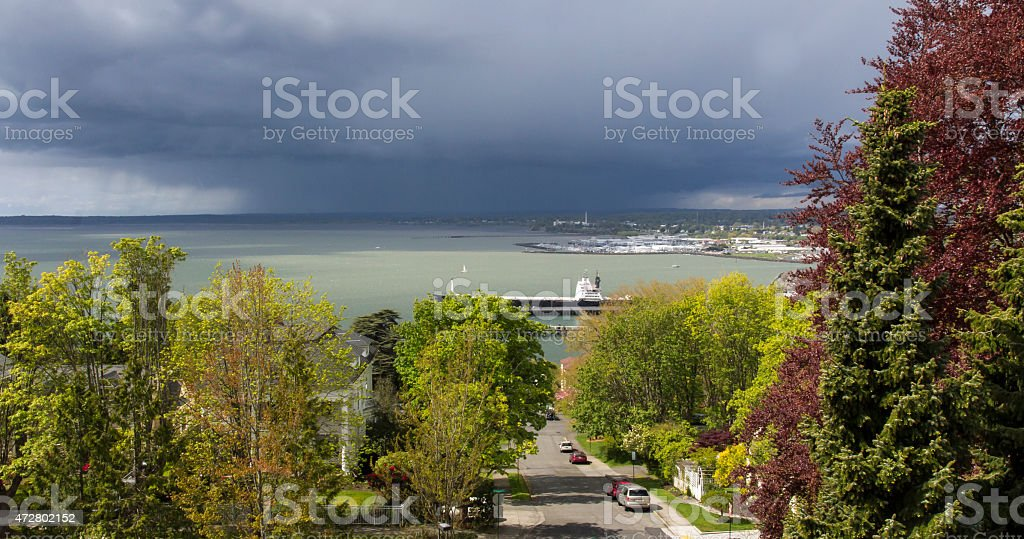 Sunny Neighborhood Overlooking a Storm Blowing in Over the Bay stock photo
