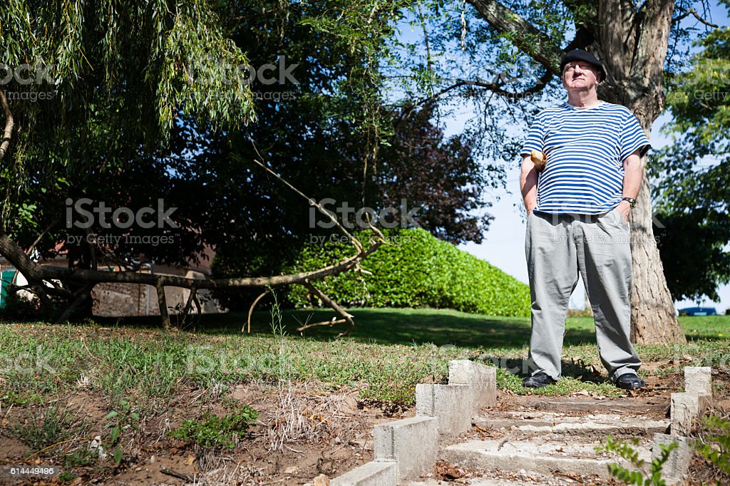 sunny senior man in striped t-shirt with baguette by steps stock photo