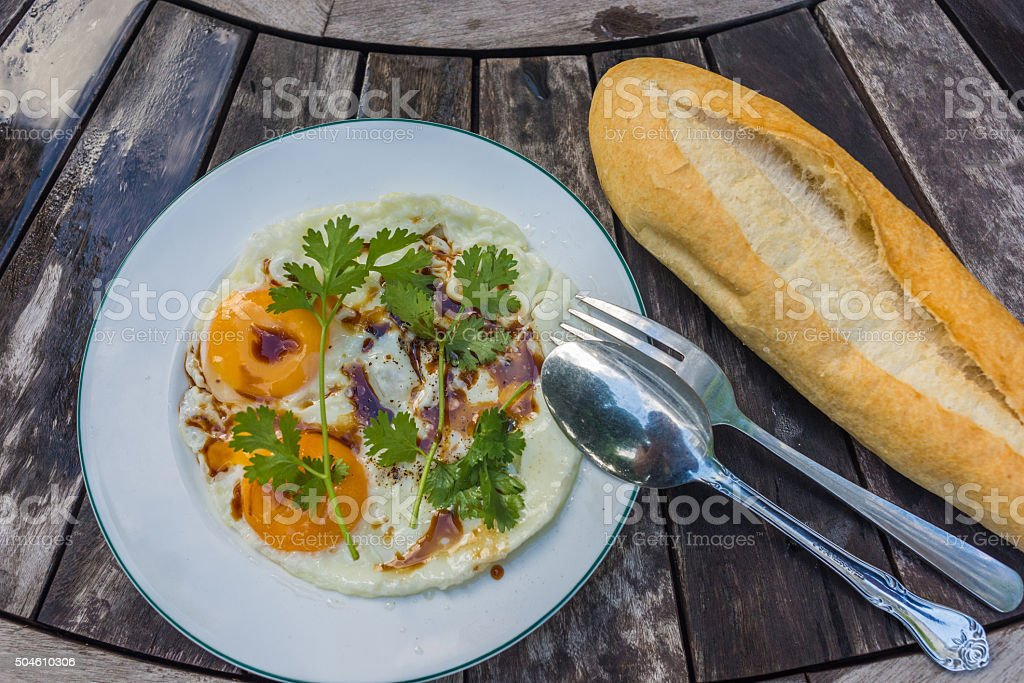 Sunny side eggs with soya sauce and coriander on surface stock photo