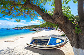 Sunny summer beach in Greece with sun beds and small