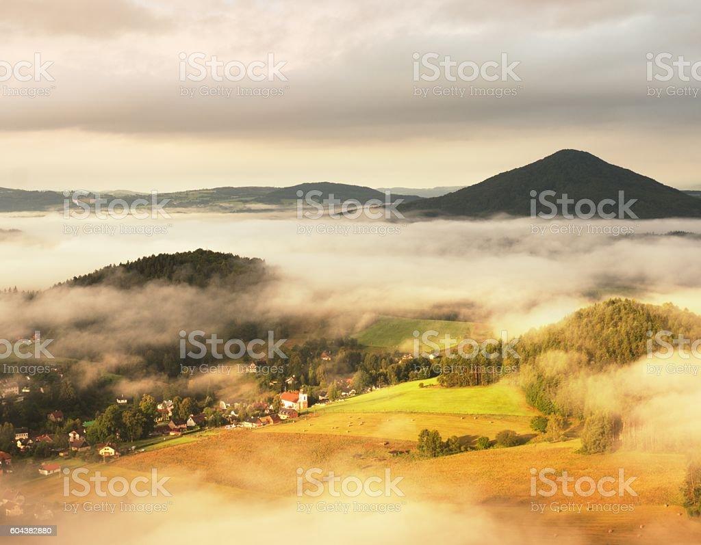 Sunny sunrise in a beautiful countryside. Fog above village church stock photo